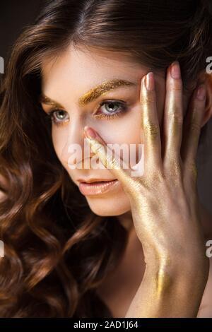 Jeune modèle avec la mode du maquillage et couverts à la main en or Banque D'Images
