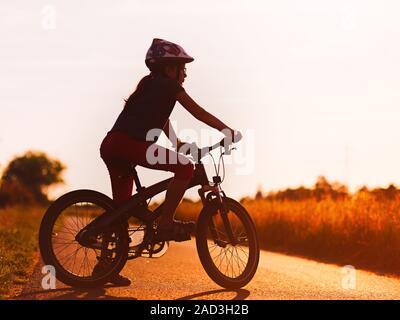 Silhouette de jeune fille sur un vélo au coucher du soleil Banque D'Images
