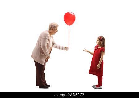 Profil de pleine longueur tourné d'une grand-mère en donnant un ballon rouge à une fille dans une robe rouge isolé sur fond blanc Banque D'Images