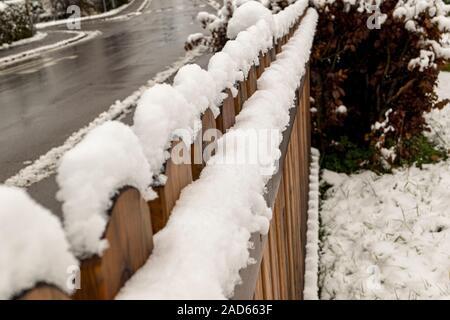 Clôture en bois avec des couronnes de neige sur la route boueuse