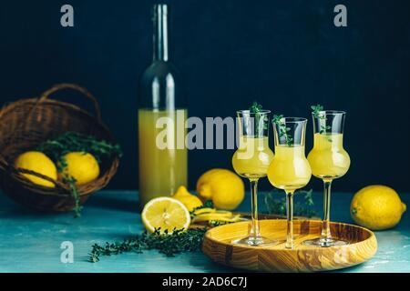 Limoncello avec le thym dans trois grappas wineglass en plateau en bois, panier de citron frais. La vie toujours artistique sur fond bleu foncé Banque D'Images