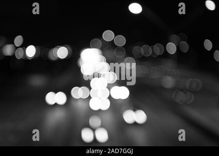 Les lumières de la ville de nuit. L'éclairage et l'éclairage. Blanc et rouge brouillé les lampes. Déménagement transport regarder dans la rue. La circulation urbaine. Voiture floue lumières nuit. Nuit urbaine. Un arrière-plan de feux. Banque D'Images