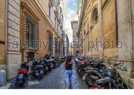 Une femme marche seul dans une petite rue latérale, avec beaucoup de motos en stationnement sur un côté ou dans le centre historique de Rome, Italie Banque D'Images