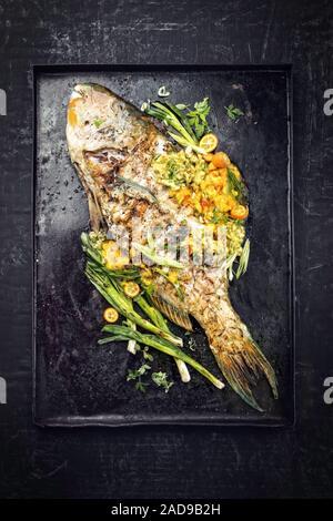Barbecue traditionnel poisson perroquet avec salsa de mangue en vue de dessus sur un tableau noir Banque D'Images