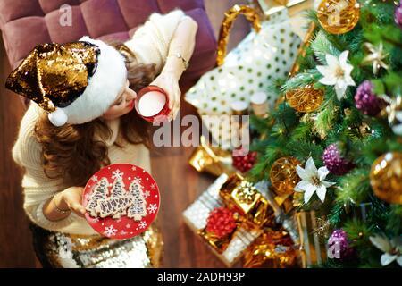 Vue supérieure de femme moderne avec de longs cheveux de brunette en or paillette jupe et pull blanc sous l'arbre de Noël décoré des boîtes près de l'actuelle m potable Banque D'Images