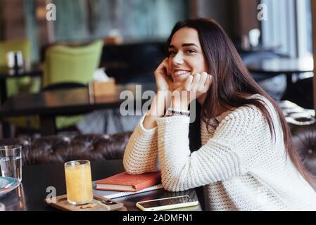 Belle femme. Cheerful blonde s'asseoir dans le restaurant avec verre jaune sur la table et sourit