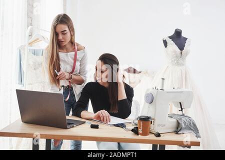 En même temps faire son bon leur bon travail. Deux créateurs de mode féminine travaille sur les nouveaux vêtements à l'atelier Banque D'Images