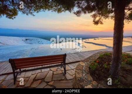Banc avec vue sur les piscines et terrasses en travertin à Pamukkale, Turquie à l'heure du coucher de soleil. Banque D'Images