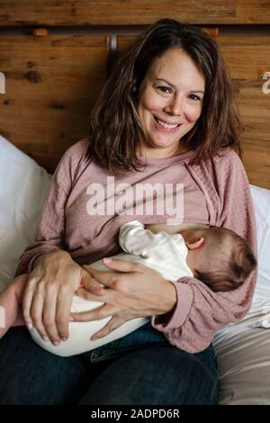 Smiling début-30'maman rose portant haut l'allaitement bébé nouveau-né Banque D'Images