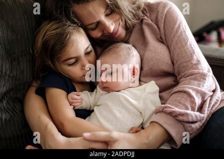 Mère embrassant 4 ans fille et bébé nouveau-né