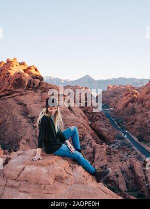 Femme portant un chapeau et rire à un point de vue dans la vallée de feu Banque D'Images