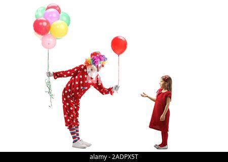 De toute la longueur d'un clown avec un bouquet de ballons en donnant un ballon rouge pour une petite fille isolée sur fond blanc Banque D'Images