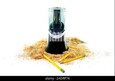 Un taille-crayon électrique entouré par des copeaux de crayon et quelques crayons gisant au fond, isolé sur fond blanc