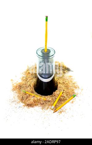 Un taille-crayon électrique entouré par des copeaux de crayon, un crayon qui sort par le haut, et quelques crayons gisant au fond, isolé sur whi