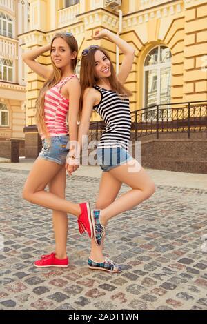 Deux jolies jeunes filles posant dans la rue en short et gumshoes Banque D'Images
