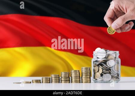 Business man holding coins mise en verre, de brandir le drapeau de l'Allemagne dans l'arrière-plan. Concept de la finance et des affaires. L'économie d'argent. Banque D'Images