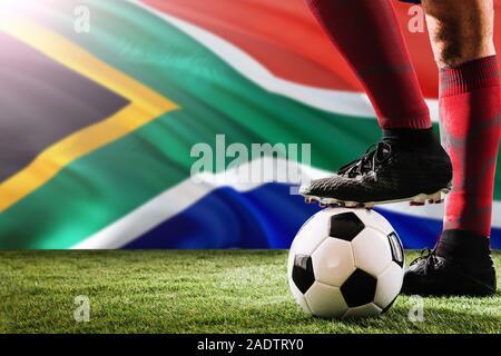 Close up les jambes de l'Afrique du Sud, l'équipe de football player en rouge chaussettes, chaussures le ballon de soccer au point de penalty ou coup franc jouant sur l'herbe. Banque D'Images