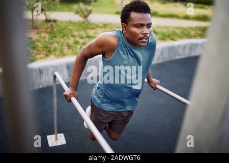 Young african american fit man doing triceps dips de barres parallèles à un sport en plein air park