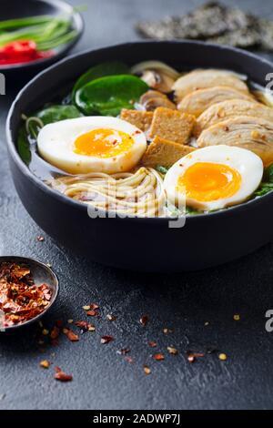 Soupe de nouilles asiatiques, ramen avec du poulet, tofu, légumes et d'oeufs dans un bol. Fond d'Ardoise Banque D'Images