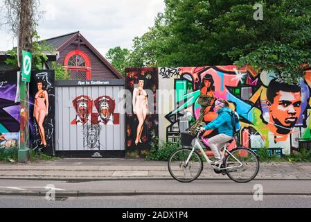 Christiania au Danemark, en vue d'une femme à vélo un passé illustre coloré clôture dans le région de Freetown alternative de Christiania, Copenhague, Danemark Banque D'Images