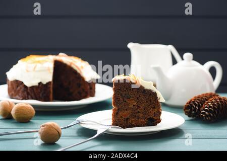 Hygge dessert. Gâteau aux fruits au chocolat avec glaçage au fromage à la crème et le zeste d'orange décoré avec les écrous et les cônes sur fond bleu copyspace closeup Banque D'Images