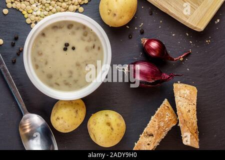 Gros plan maison soupe aux lentilles à la crème du dessus avec ingrédients sur fond noir texturé Banque D'Images