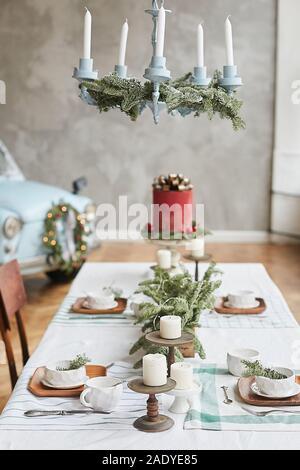 Table de fête servi pour le brunch de Noël avec de beaux plats de fête, verre, candélabres avec des bougies et des branches de sapin. La veille de Noël. Nouvelle année Banque D'Images