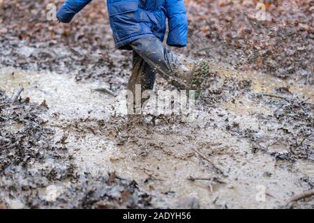 Les jeunes enfants jouant dans une flaque de boue Banque D'Images