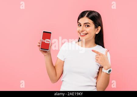 Kiev, UKRAINE - 20 septembre 2019: jolie brunette girl pointing with finger at smartphone avec l'app isolé sur pink Banque D'Images