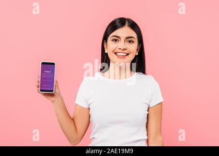 Kiev, UKRAINE - 20 septembre 2019: jolie brunette smiling girl holding smartphone avec l'application Instagram sur rose isolé Banque D'Images