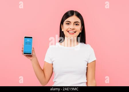 Kiev, UKRAINE - 20 septembre 2019: jolie brunette smiling girl holding smartphone avec l'application Skype sur rose isolé Banque D'Images