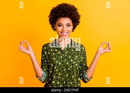 Photo de belle peau sombre dame tenant la main position om relaxation méditation matin rafraîchissement corps porter chemise pointillée verte jaune isolé