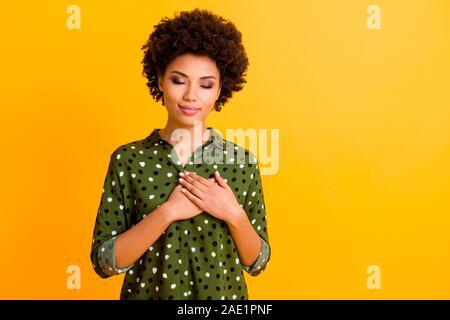 Portrait of African American girl inspiré calme toucher sa poitrine crois palm bien paraître sentiments reconnaissants porter des vêtements élégants briller plus isolé vert Banque D'Images
