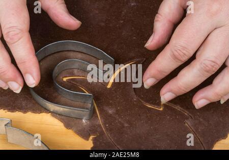 Emporte-pièce métallique sur la pâte d'épices détail et femmes. Une coupe en forme de fer à cheval, les bonbons de Noël pâtisserie brutes laminées sur bois. Banque D'Images