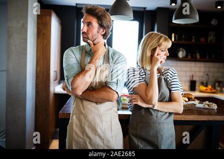Malheureux couple having argument et lutte dans la cuisine qui mène au divorce Banque D'Images