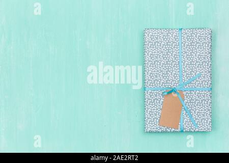 Vue de dessus sur un enveloppés dans des cadeau pour anniversaire, Noël, ou autre célébration sur fond de bois turquoise. Boîte-cadeau avec ruban et étiquette. Birthd Banque D'Images