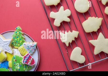 Mise à plat des biscuits de Noël sur plaque et sur la grille du four biscuits décorés avec fond rouge contre un minimum de créativité et de food concept. Banque D'Images