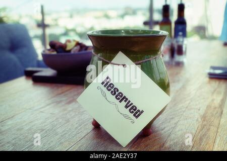 Réservés signe sur table de restaurant, terrasse extérieure d'été, l'image aux tons doux, effet grainé Banque D'Images