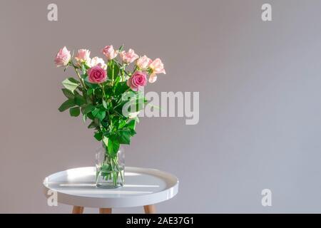 Des roses rose pastel vase en verre sur table de café blanc sur fond neutre. Banque D'Images