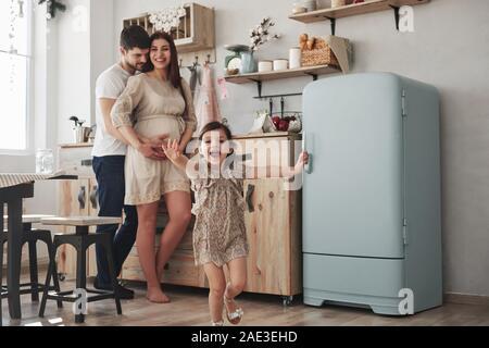 Famille heureuse. Enfant de sexe féminin ludique s'amuser en exécutant dans la cuisine dans la journée d'avant de sa mère et de son père Banque D'Images