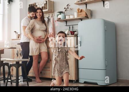 Les personnes gaies. Enfant de sexe féminin ludique s'amuser en exécutant dans la cuisine dans la journée d'avant de sa mère et de son père Banque D'Images