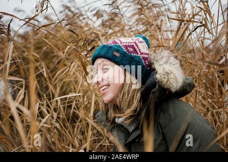 Portrait de femme à la curieux tout en jouant à l'extérieur dans l'herbe