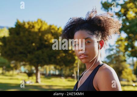 Portrait d'une jeune femme afro-américaine de remise en forme avec des écouteurs dans les oreilles à écouter de la musique au parc avant de faire l'exercice sur une journée ensoleillée Banque D'Images