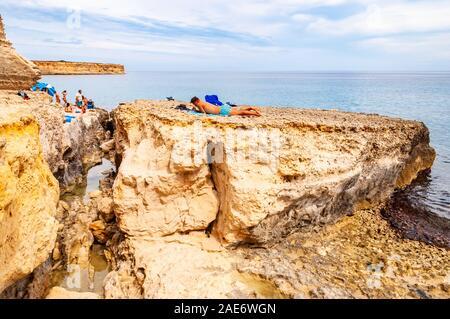 Torre Sant'Andrea, Pouilles, Italie - 09 septembre 2019: Les gens de la falaise sous-marine, bain de soleil, nager dans l'eau de mer cristalline on Rocky beach Banque D'Images