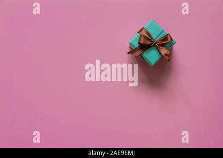Cadeau turquoise ou présenter fort avec ruban brun sur rose Vue de dessus de table. Mise à plat. Anniversaire, un mariage ou Noël concept. Banque D'Images