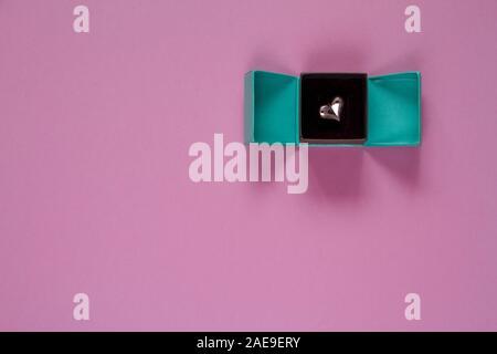 Turquoise ouvert cadeau ou présent fort avec un coeur rose sur l'intérieur de la table view. Mise à plat. Anniversaire, un mariage ou Noël concept. Banque D'Images