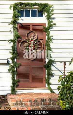 Couronne de Noël décoration de porte, Colonial Williamsburg. Les gousses séchées Lotus rouge, grenades, bâtonnets torsadés, sur bois à la porte marron, evergreen swag.