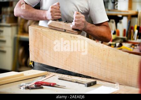 Menuisier travaillant avec une raboteuse sur un bloc de bois le lissage de la surface dans un gros plan de ses mains et des outils sur l'établi