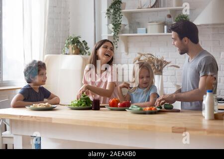 Happy Family avec les enfants préparer une salade de légumes dans la cuisine domestique Banque D'Images