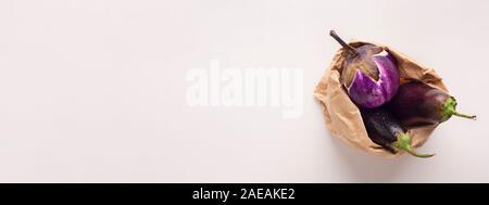 Aubergines bio en sac de papier déchets zéro on white Banque D'Images